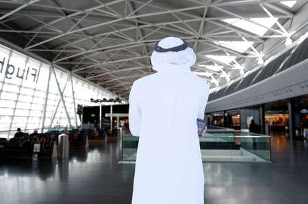 Travelling Arabic man thinking while inside airport wearing traditional kandora thawb menswear