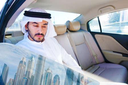 Arab UAE rich man inside a luxury car with reflection of Dubai cityspace from the window