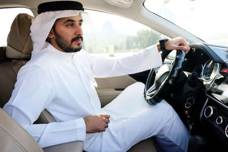 Handsome Arabic man sitting on car front seat holding the wheels ideal for vehicle loan, insurance policy or corporate mock up