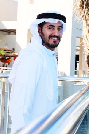 Handsome Arabic guy looking happy and smiling wearing kandoora dishdasha
