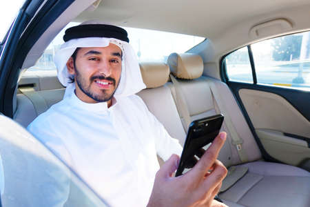 Happy positive Arab man holding his cellphone while reading a good news about the market, economy or forecast,