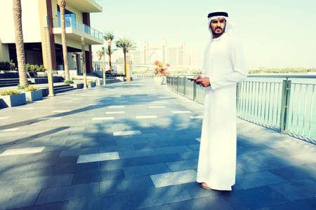 Portrait of Arab man with smart phone wearing traditional Gulf men's wear