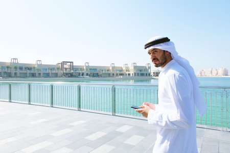 Middle East Arab man walking on bricks wearing thawb kandura with copy space