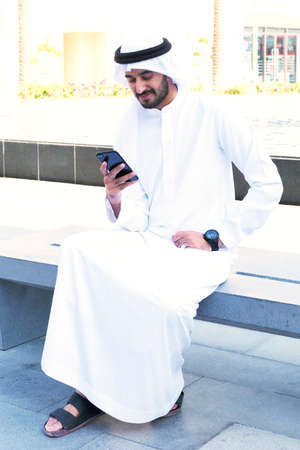 Middle Eastern Arab man chatting on mobile phone while sitting outdoors 스톡 콘텐츠