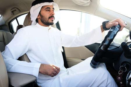 Middle Eastern Arabian man driving car wearing traditional gulf menswear called kandura
