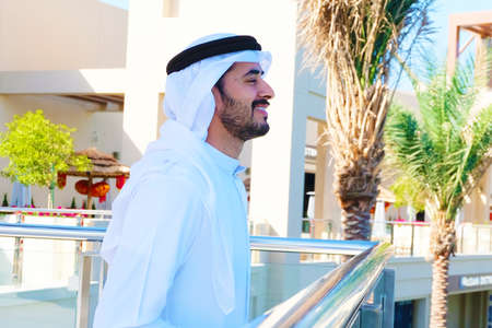 Close up of Middle Eastern Arabic guy side view smiling on sunny day wearing traditional Emirati kandora men's wear