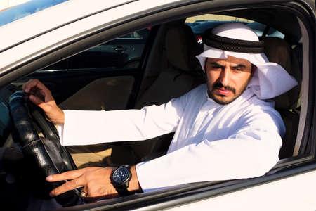 Middle Eastern Arab man driving a car  wearing traditional UAE menswear 스톡 콘텐츠
