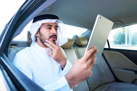 Anxious Middle Eastern Arab business man reading the news, market, or forecast on his tablet device.