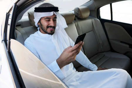 Happy Arab business man reading the news about the market, trends or economy update in the Middle East.