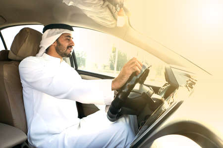 Arab corporate business man driving a luxury car during sunny daytime
