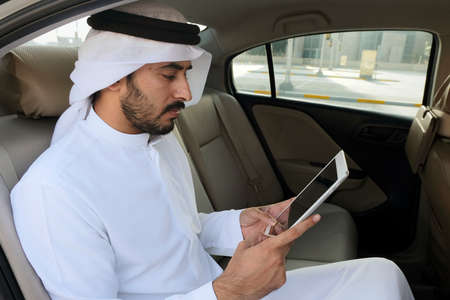 Chatting or SMS mock up of Arab man while sitting on car back seat