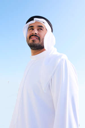 Modern Arabic Middle Eastern man smiling on isolated background wearing traditional UAE dress