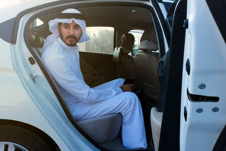 Emirati Man from the Middle East Gulf at a car backseat wearing dishdash 스톡 콘텐츠