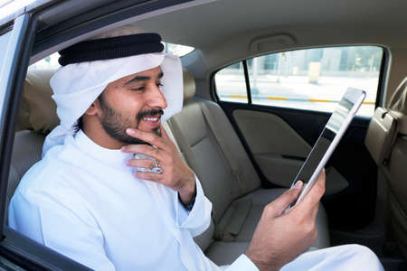 Happy Smiling Arabic man about the positive financial market, news, or economy forecast reading on a table device while inside a luxury car