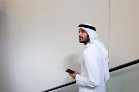 Muslim Arab male model on a vertical escalator holding a mobile phone device 스톡 콘텐츠