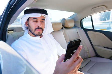 Optimistic Arab business man reading the news about the market, trends or economy update in the Middle East. 스톡 콘텐츠