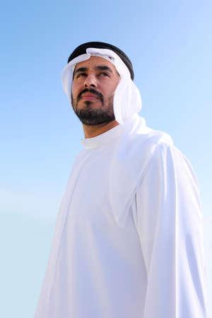 Emirati Arab man wearing traditional UAE kandora garment on isolated sky background