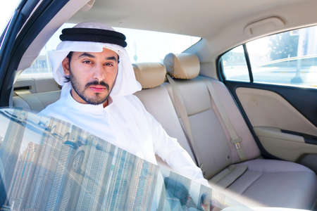 Handsome Arab business man inside a luxury car looking at city buildings and towers