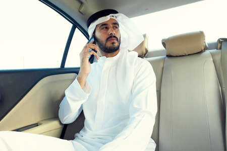 Close up of Inspired Arab man on the phone talking about business while inside a car 스톡 콘텐츠