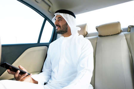 Smiling Middle Eastern Arab businessman as he rides a luxury transportation service