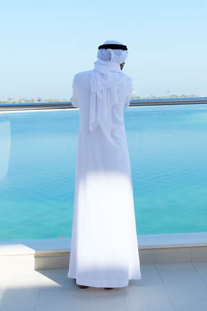 Arabian business man standing on his back while looking far away