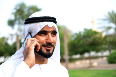 Happy Arabic Man talking on his smart mobile phone device with positive face mock up and copy space 스톡 콘텐츠