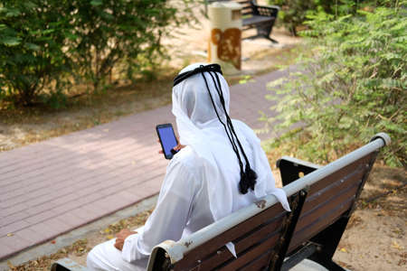 Local Arabic man pressing on his smart mobile phone or reading mock up