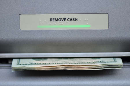 maching: American cash being dispensed from a bank automated teller maching, or ATM