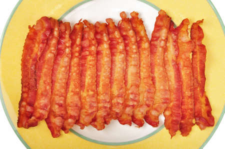 Strips of cooked bacon on a yellow plate Foto de archivo