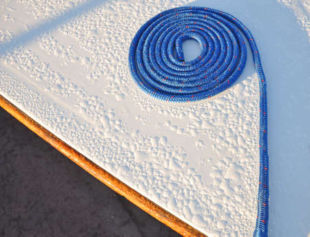 coiled: neatly coiled length of rope on the bow of a small sail boat Stock Photo