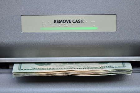 automatic transaction machine: Efectivo americano que se dispensa desde un maching banco cajero automático o ATM Foto de archivo