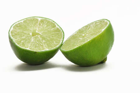 two lime halves with vibrant but natural coloring isolated on white