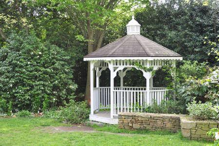 Peaceful gazebo set in the shade of a mature garden Standard-Bild