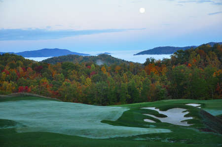 nestled: golf course nestled in the North Carolina mountains in the Fall just as the morning fog lifts in the valleys Stock Photo