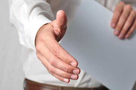 Open handshake and paperwork pose conveying job interview or acceptance Stock Photo