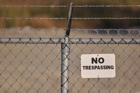 chain link fence: No trespassing sign hanging on a menacing barbed wire fence Stock Photo
