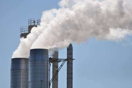Smoke stacks billowing out steam and vapor from a manufacturing facility Stock Photo - 15216928