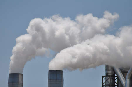 smoke stack: Smoke stacks billowing out steam and vapor from a manufacturing facility
