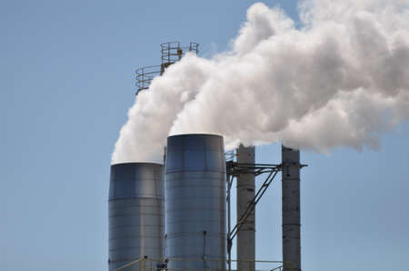 Smoke stacks billowing out steam and vapor from a manufacturing facility Stock Photo - 15216938