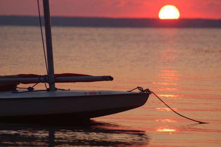 Afgemeerd sailboad met een ondergaande zon achtergrond Stockfoto