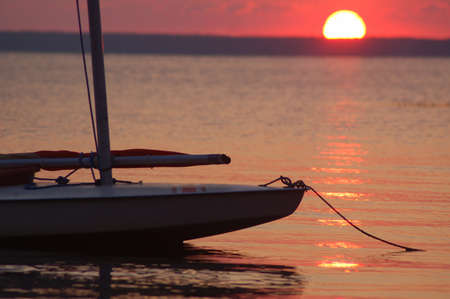 Moored sailboad with a setting sun background