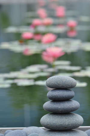 zen water: Stack of weathered river stones against a peaceful water garden background