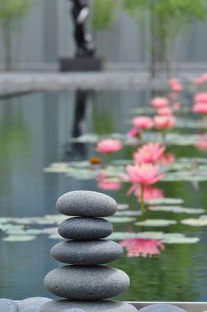 Stapel verweerde rivier stenen tegen een rustige watertuin achtergrond Stockfoto