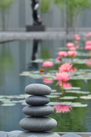 Stack of weathered river stones against a peaceful water garden background