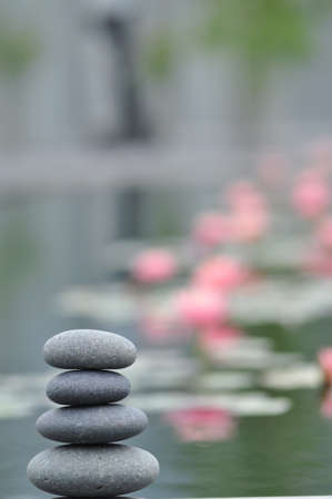 Stack of weathered river stones against a peaceful water garden background Stock Photo - 15216933