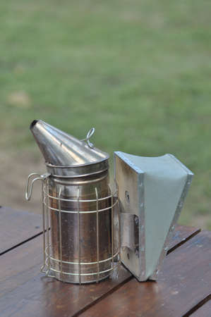 Manual bee fogger used to blow smoke into hives and put honey bees to sleep photo