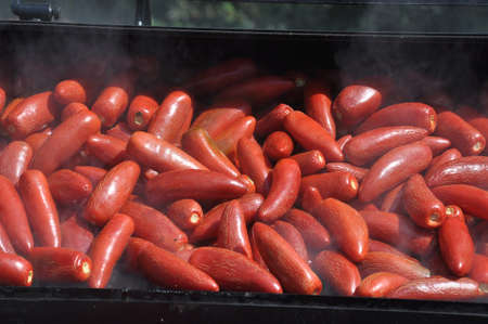 Grote partij hot chili peppers worden gerookt op een grill
