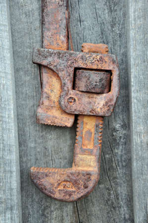 corrode: Rustic antique wrench hanging on a barn wall Stock Photo