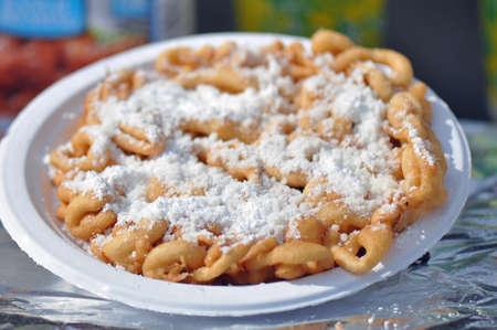 Fried dough funnel cake or elephant ear sold at north; carolina; state; fair; street; food; snack; salt; fried; fry; french; carnival; america, elephant, ear, funnel, cake, sweet, powdered, sugar, dessert, dough, oil Stock Photo