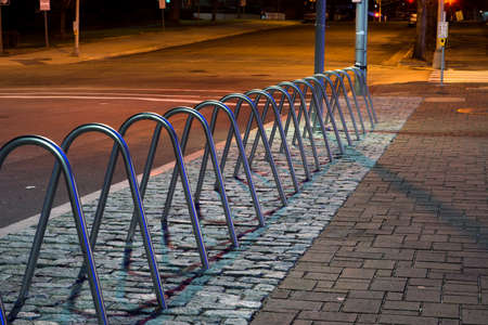 rack wheel: Night photo of a metal bicycle rack in downtown Raleigh, North Carolina